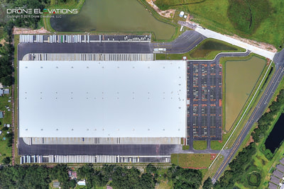 Overhead aerial drone photo of distribution center warehouse.